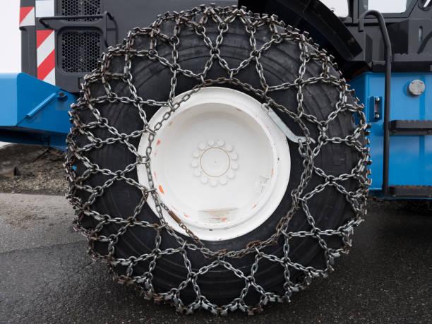 sneeuw ketting rond grote wiel van bulldozer - tractieapparaat stockfoto's en -beelden