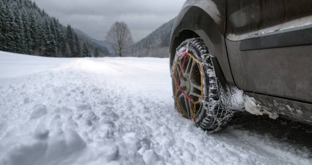 Snow chains on tire at winter road stock photo