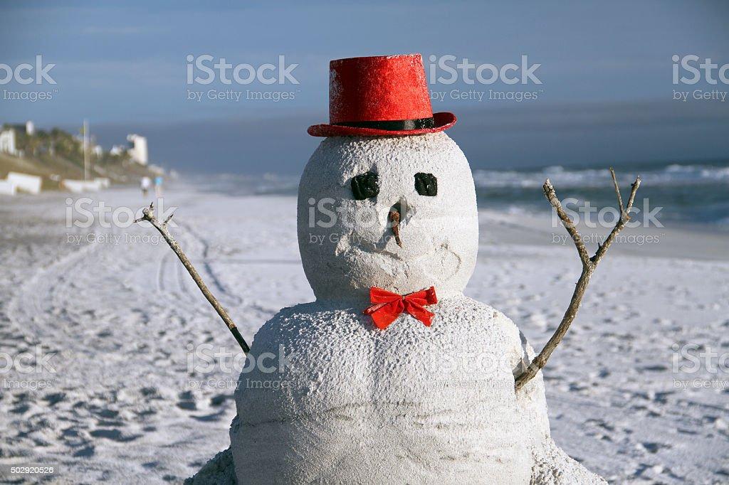 Snow Christmas snowman in santa hat at sandy beach stock photo