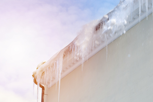 snow cleaning from rooftop outdoors at sunny day. roof icicle problem concept.