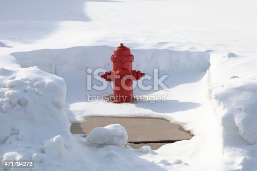 Snow cleared red fire hydrant. Community service oriented. Hydrants are cleared after a large snow storm. Vibrant red color against the white and blue and gray of the snow. Good for cropping or copy placement. XXXL size.