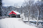 a red bridge is snow covered in the winter