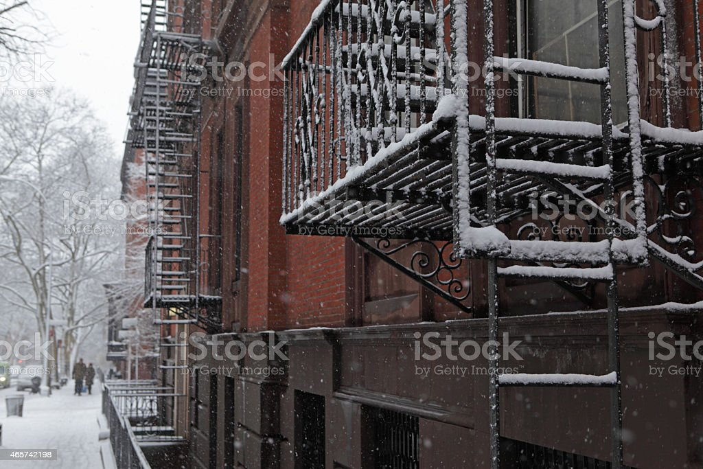 Snow covered Brooklyn brownstone townhouse fire escape in winter stock photo