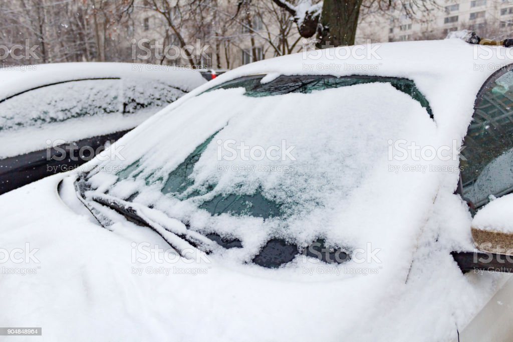 Snow covered car in the parking lot. Car in winter