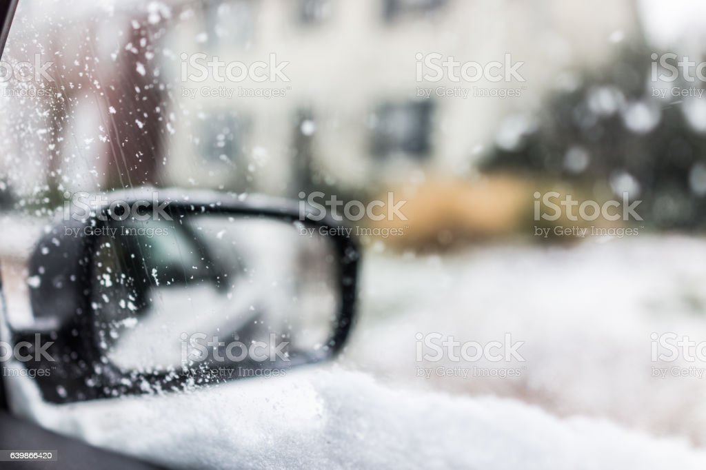 Snow covered car window glass view from inside with mirror