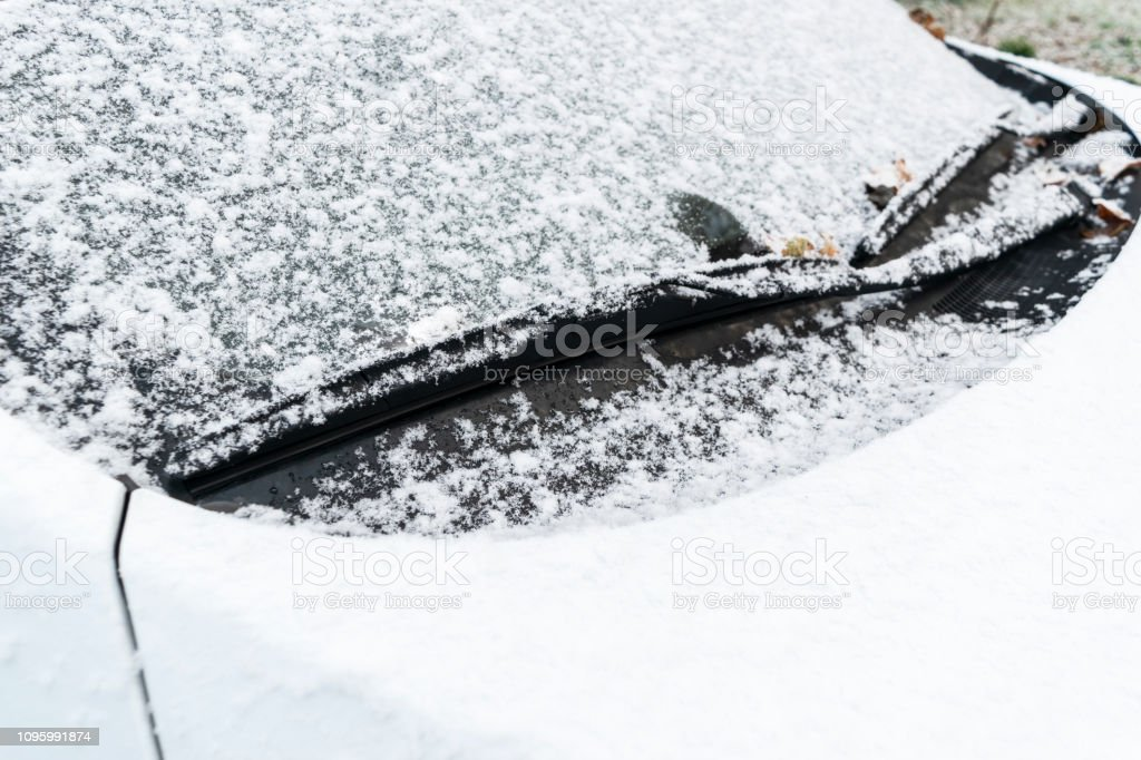 Snow covered car window with wipers, macro, close up. Car wiper...