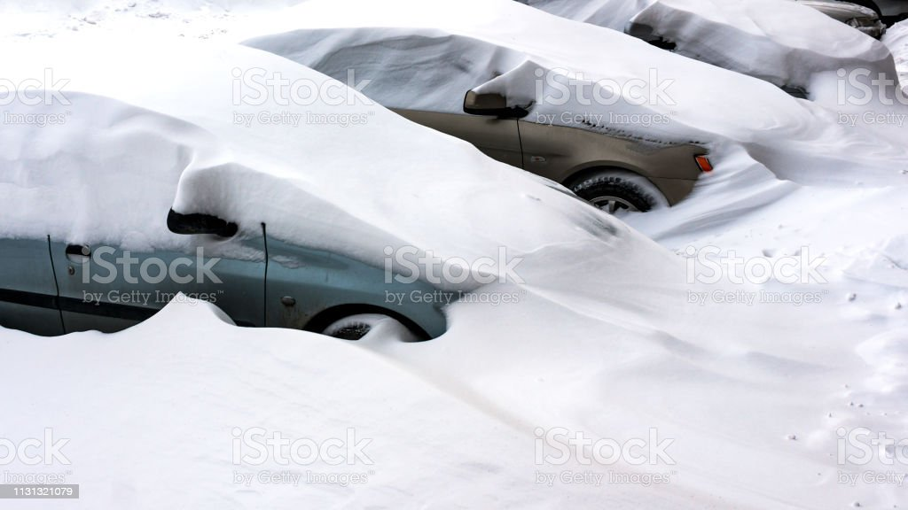 Snow covered cars after snowfall at winter day. The parked cars in...