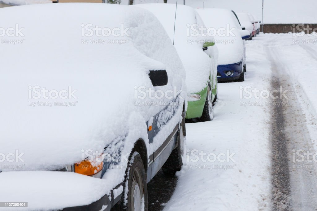 Snow covered cars parked of the side of the road