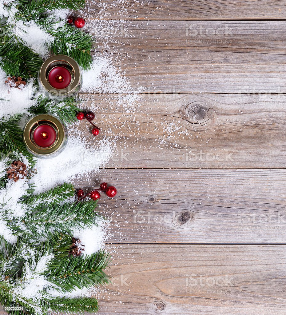 Snow covered Christmas fir branches and candles on rustic wooden royalty-free stock photo
