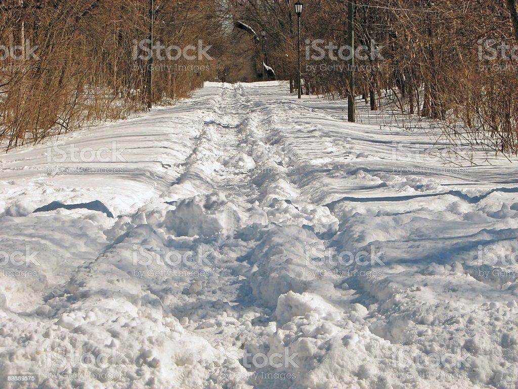 Camino cubierto de nieve en invierno y de pisadas foto de stock libre de derechos