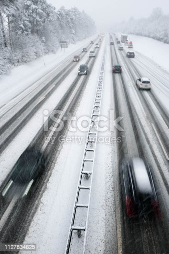 1127834626 istock photo snow covered highway in austria with cars out of focus 1127834625