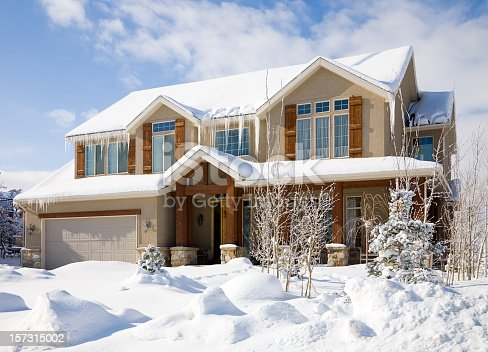 A snow covered luxury home under blue sky.