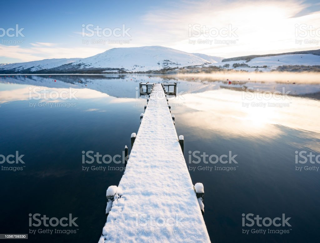 Snow covered jetty on Loch Earn in Scotland stock photo