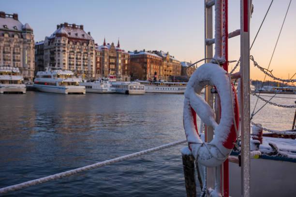 en snötäckt livskonserver som förvaras på en vattentaxi som ligger dockad i en hamn i stockholm vid en vintersoluppgång. - ferry lake sweden bildbanksfoton och bilder