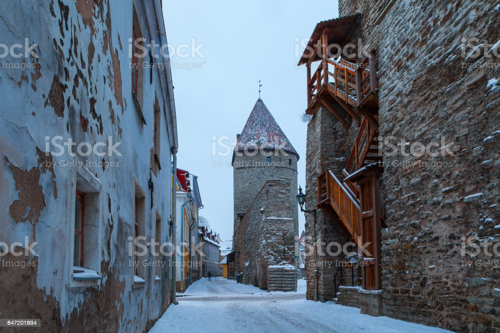 Snow covered magic winter view of old street in Tallinn, Estonia. Cold toned picture with ancient wall and towers. stock photo