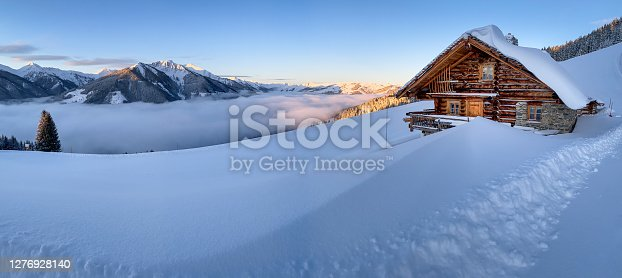 istock Snow covered mountain hut old farmhouse in the ski region of Saalbach Hinterglemm in the Austrian alps at sunrise 1276928140