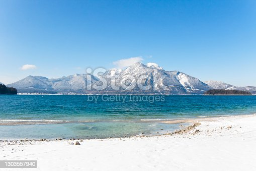 Snow covered mountain on a snowy shore of a mountain lake in Upper Bavaria, Germany.