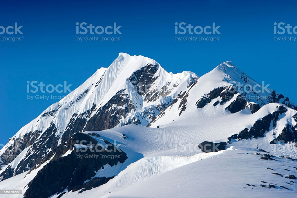 Snow covered mountain peak on a sunny day royalty-free stock photo