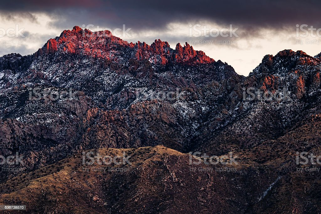 Snow covered mountain peaks at sunset stock photo