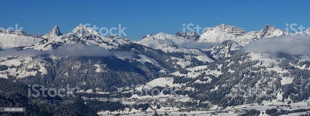 Snow covered mountain range in Saanen stock photo