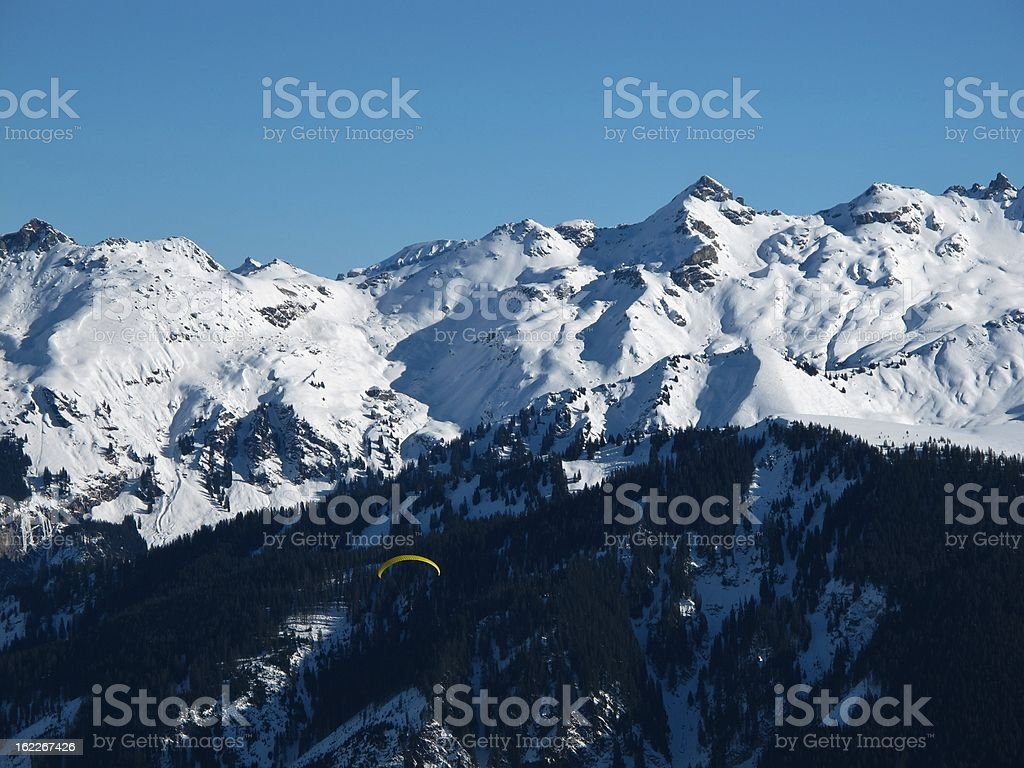 Snow covered mountains and paraglider stock photo
