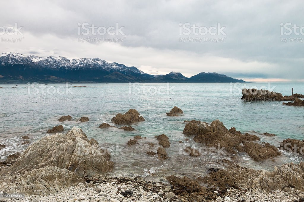 Snow covered mountains on ocean shore stock photo