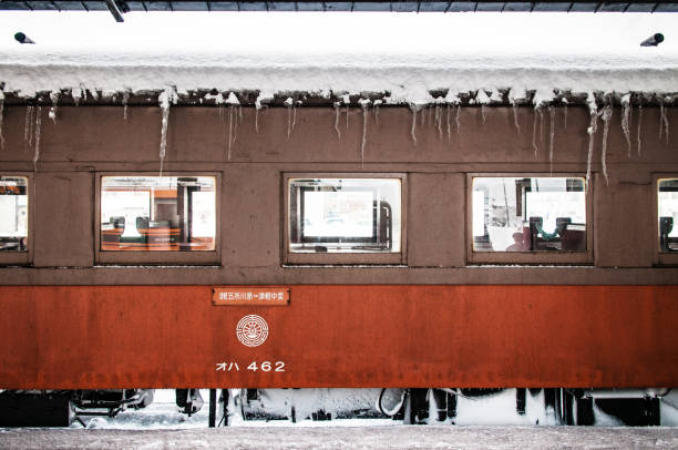 snow covered orange vintage train of tsugaru railway line waiting for passenger at goshogawara station, famous sightseeing train of aomori. - goshogawara zdjęcia i obrazy z banku zdjęć