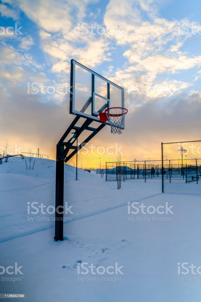 Snow covered outdoor basketball court at sunset. Snow covered outdoor...