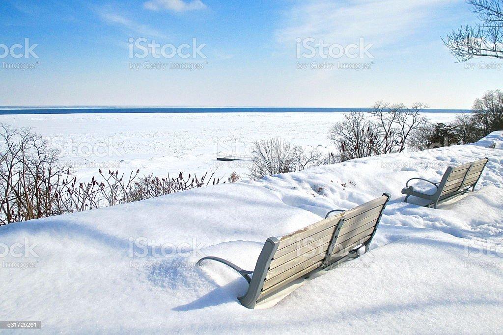 Bancs recouverts de neige sur la neige recouvert le lac photo libre de droits