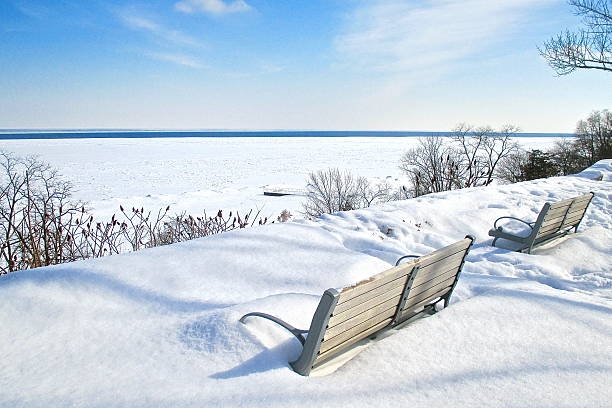 Snow covered park benches overlooking snow covered lake stock photo