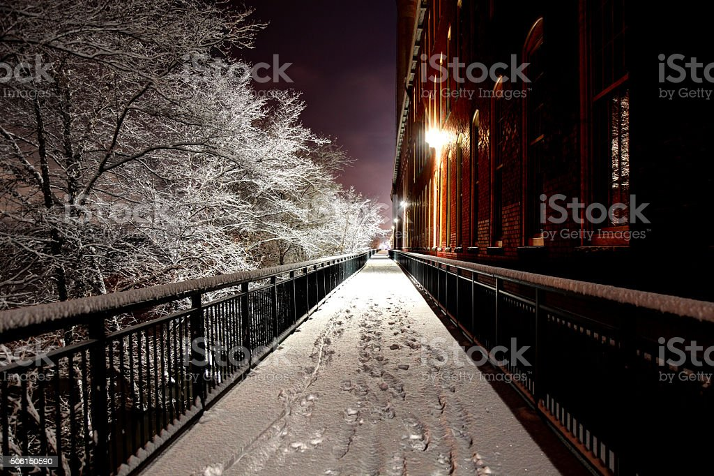 Snow covered path along Lowell's Riverwalk stock photo