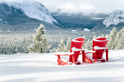 Snow Covered Red Adirondack Chairs in front of a Forested Valley
