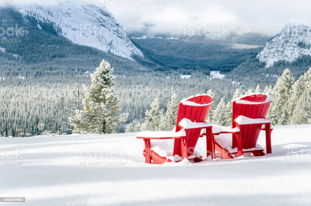 Snow Covered Red Adirondack Chairs in front of a Forested Valley stock photo