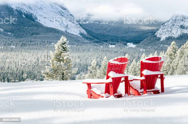 Photo of Snow Covered Red Adirondack Chairs in front of a Forested Valley