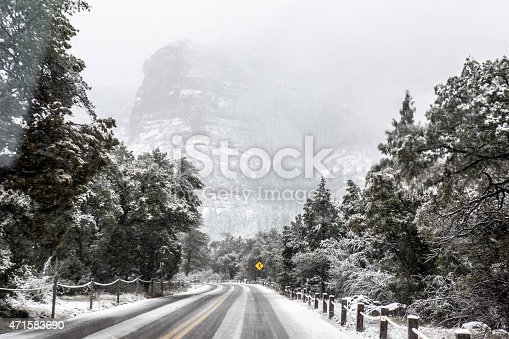 A foggy day after an unexpected snow storm in March in Sedona, Arizona. The unexpected storm covered roads, trees and mountains with snow.  This made for dangerous driving conditions. Shot was taken from a car giving the drivers perspective of the road.  Taken with Canon 5D Mark 3.  rm