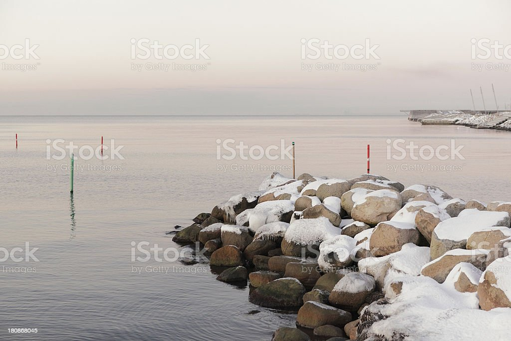 Snow covered rocks at shoreline royalty-free stock photo