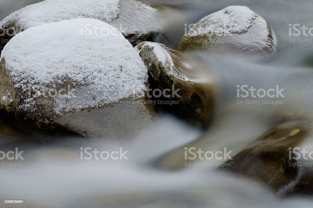 snow covered rocks on mountain river stock photo