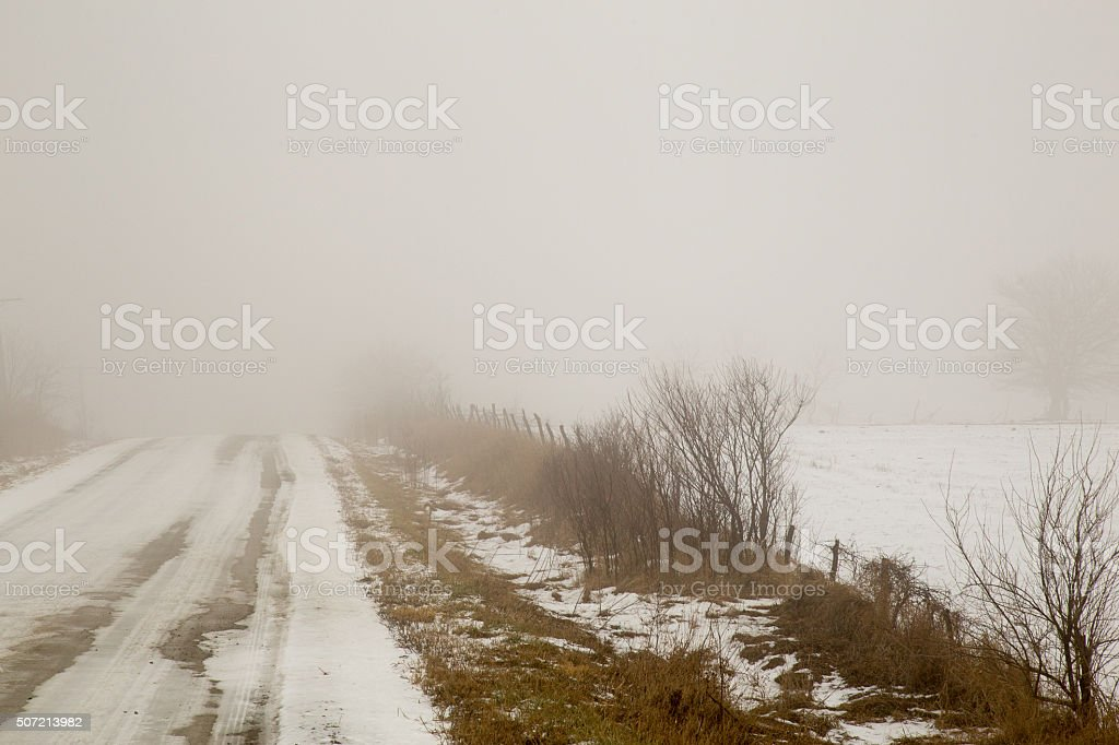 Snow Covered Rural Dirt Road And Farm Field stock photo
