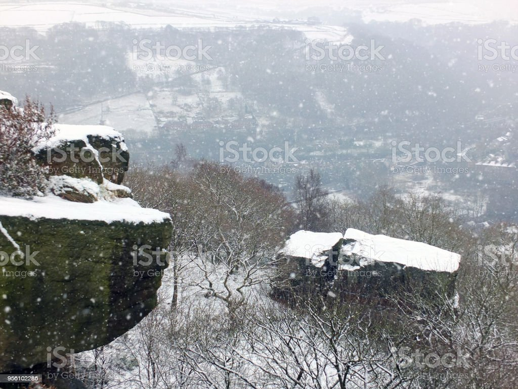 snow covered stone outcrops at hellhole rocks near hebden bridge in west yorkshire in winter snow with the calder valley and woodland stock photo