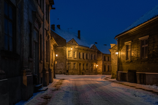 Snow covered street of Kuldiga old town during blue hour lit by a street lamps.