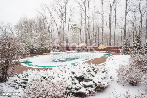 Snowy backyard with white bushes and snow covered swimming pool in late March during an unexpected snowfall in southern Indiana
