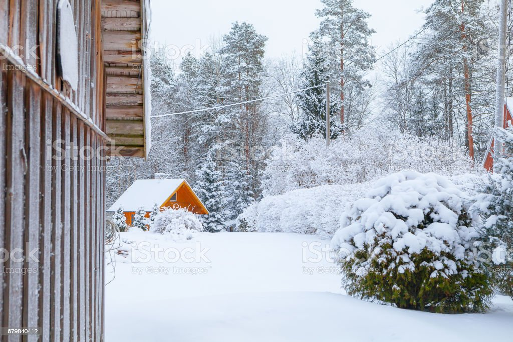 Snow covered yard of wooden cottages stock photo