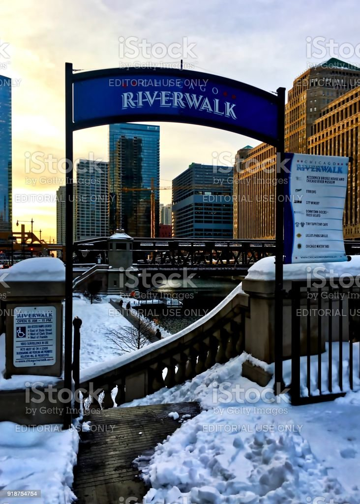 Snow covering urban landscape of Chicago Loop after winter storm, while sun sets over entrance to the riverwalk at Chicago River. stock photo