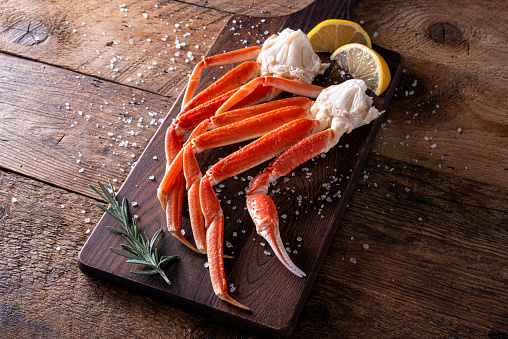 Delicious snow crab leg clusters on a rustic wood table top.
