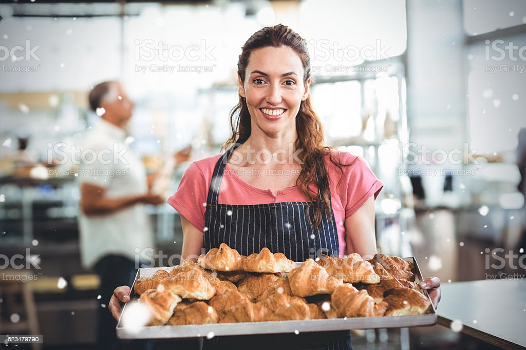 Snow falling against  baker showing tray of fresh croissant stock photo