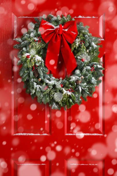 schnee fällt vor roten tür mit kranz geschmückt - deko hauseingang weihnachten stock-fotos und bilder