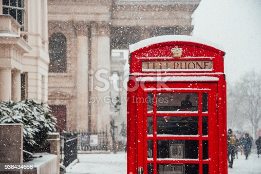 Snow falling over London - Snow flakes falling by a red telephone booth