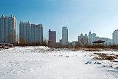 Snow field and city skyscraper.