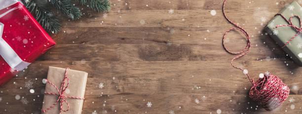 schneeflocken fallen auf geschenke auf einem hölzernen tisch-banner mit textfreiraum - weihnachtsessen ideen stock-fotos und bilder