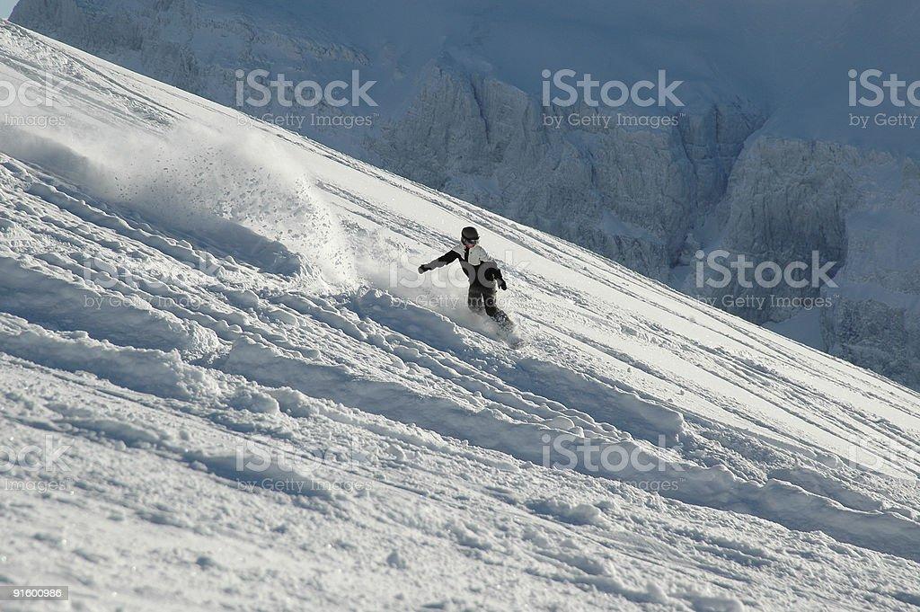 Snow flies as snowboarder rides the powder royalty-free stock photo